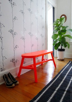Neon-orange-bench-in-a-modern-hallway-with-white-black-plant-wallpaper-and-laminate-wood-floor-design-ideas